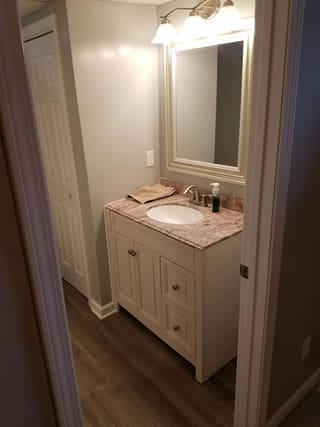 Installation of a new bathroom vanity including mirror and new flooring also installed.